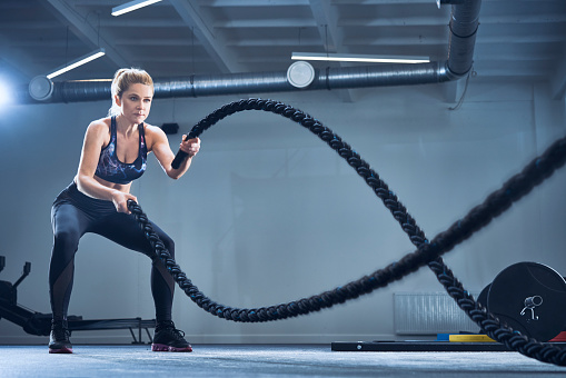 Athletic woman exercising with battle ropes at gym - gettyimageskorea