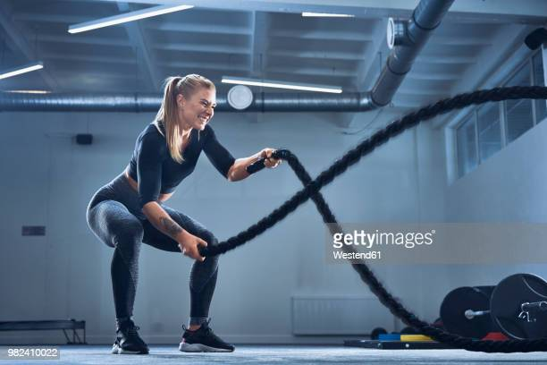 athletic woman exercising with battle ropes at gym - crossfit stock pictures, royalty-free photos & images