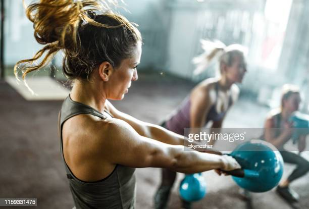 athletic woman exercising with kettle bell on a class in a health club. - sports training stock pictures, royalty-free photos & images
