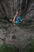 Athletic woman hanging in one hand on craggy rock wall