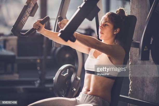 femme athlétique ayant formation sur appareil d'exercice dans une salle de gymnastique sportive. - forte poitrine photos et images de collection