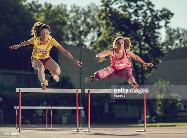 Athletic woman hurdling on a sports race.