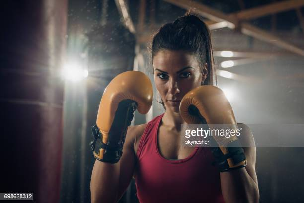 Athletic woman in a boxing fighting stance at health club.