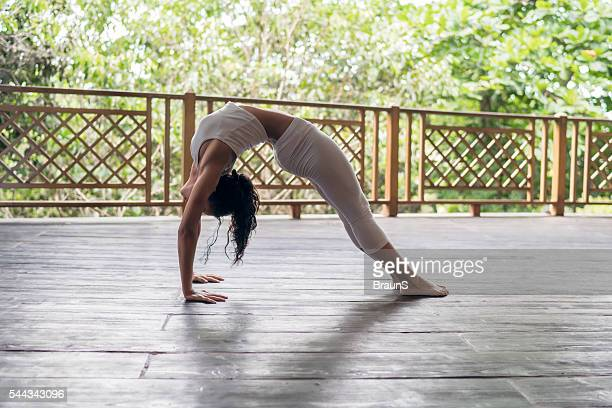 Athletic woman in a bridge position on a terrace.