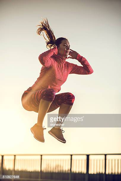 Athletic woman jumping high up at sunset.