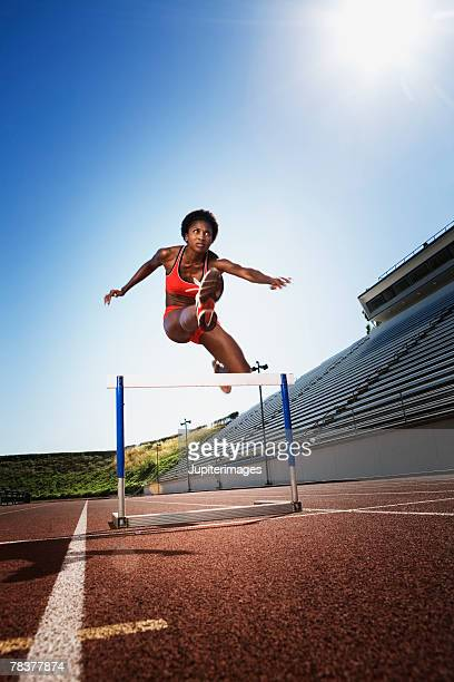 athletic woman jumping over hurdle - hurdle stock photos and pictures