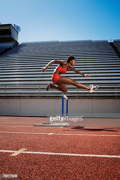 athletic woman jumping over hurdle - women's track fotografías e imágenes de stock