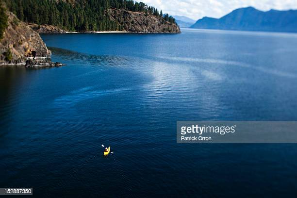 A athletic woman kayaking on a lake in Idaho.