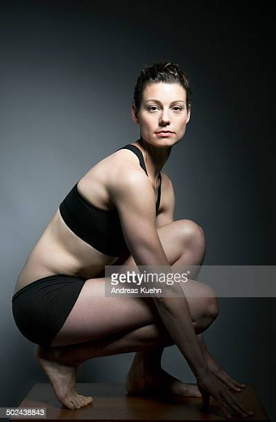 Athletic woman kneeling down, portrait.