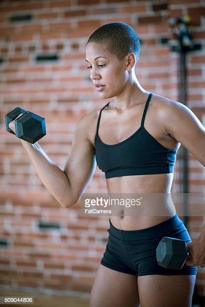 athletic woman lifting weights - black female bodybuilder stock photos and pictures