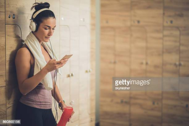 athletic woman listening music and text messaging on smart phone at gym's locker room. - locker room stock pictures, royalty-free photos & images