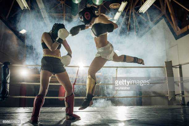 Athletic woman making a flying move on a kickboxing match with her sparing partner.