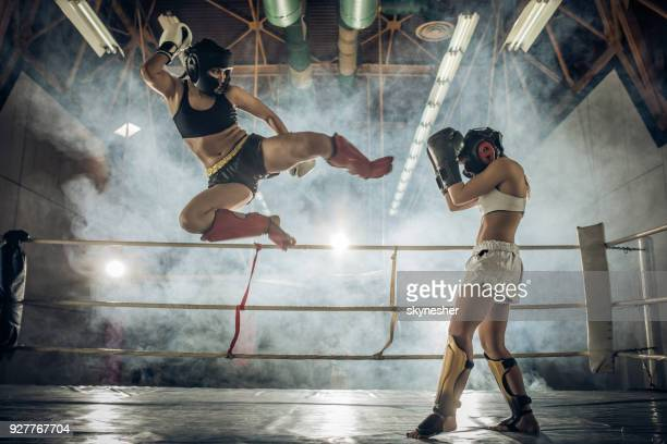 athletic woman making a flying move on a kickboxing match with her opponent. - mma stock pictures, royalty-free photos & images
