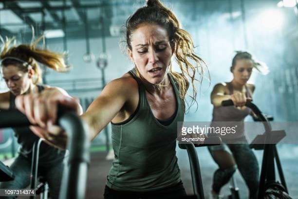 sportieve vrouw het maken van een inspanning tijdens de oefening les op fiets in een sportschool. - inspanning stockfoto's en -beelden