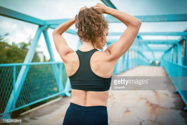 athletic woman making ponytail before sports training - tighten stock pictures, royalty-free photos & images