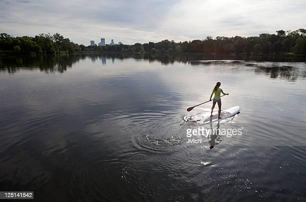 athletic woman stehpaddeln auf den ruhigen see des mittleren westens. - minneapolis stock-fotos und bilder