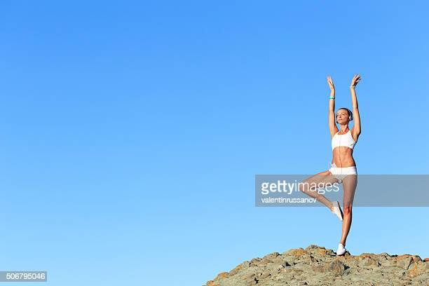 Athletic woman practicing on top of rock