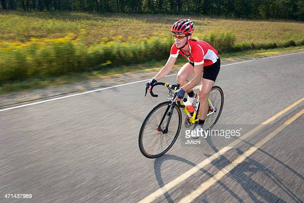 Athletic Woman Riding Road Bicycle on a Rural Road.