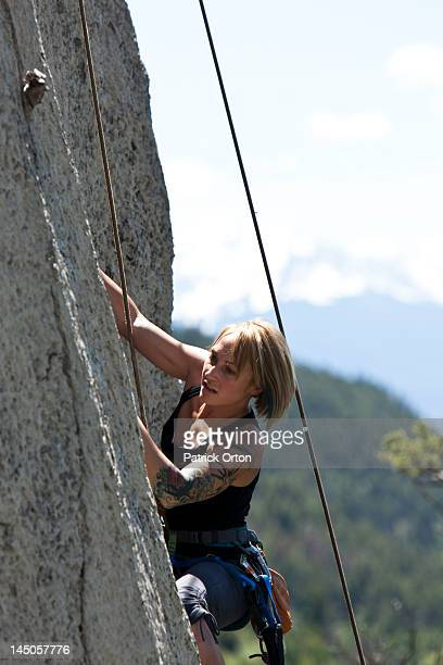 A athletic woman rock climbing high off the ground in Montana.