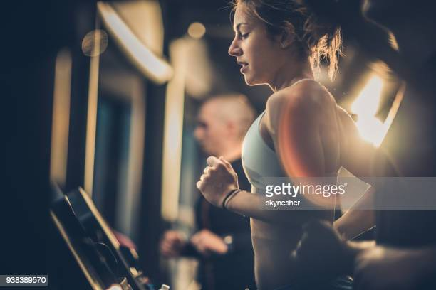 athletic woman running on treadmills during sports training in a health club. - sports training stock pictures, royalty-free photos & images