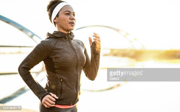 athletic woman running outdoors - headband stock pictures, royalty-free photos & images