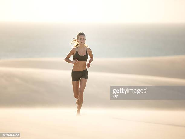 Athletic woman running over a Sand Dune, Extreme Fitness