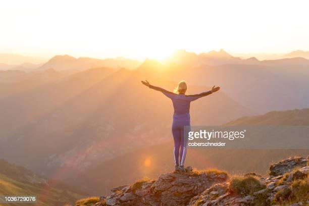 athletic woman standing on a mountain ridge at sunrise, gastein, salzburg, austria - sunrise mountain peak stock pictures, royalty-free photos & images
