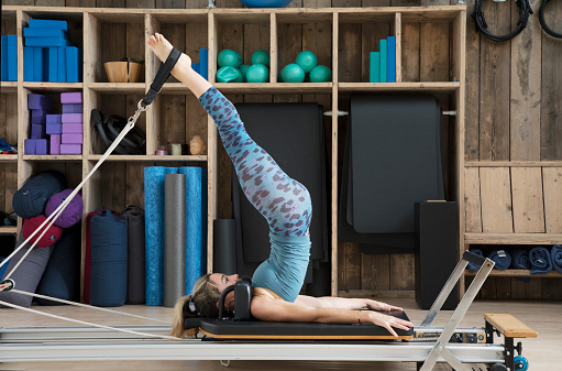 Athletic woman stretches on pilates reformer with legs in straps. - gettyimageskorea