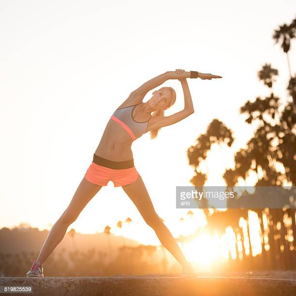 Athletic Woman Stretching at the Beach at Sunset