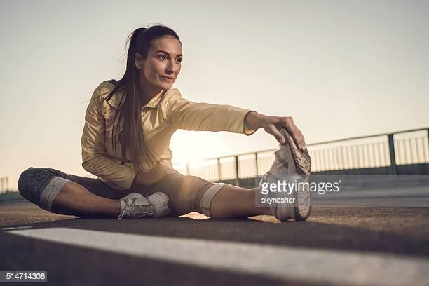 競技の女性彼女の脚ストレッチ日没にます。