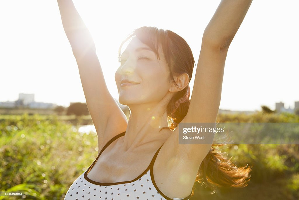 Athletic woman stretching in nature : Stock Photo