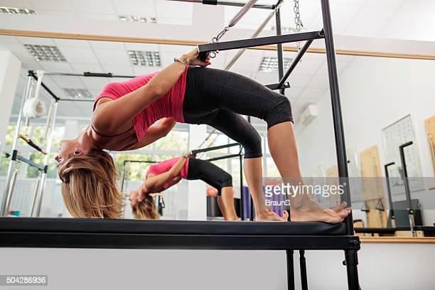 mulher atlética alongamento em uma máquina de pilates na academia de ginástica. - reformista - fotografias e filmes do acervo