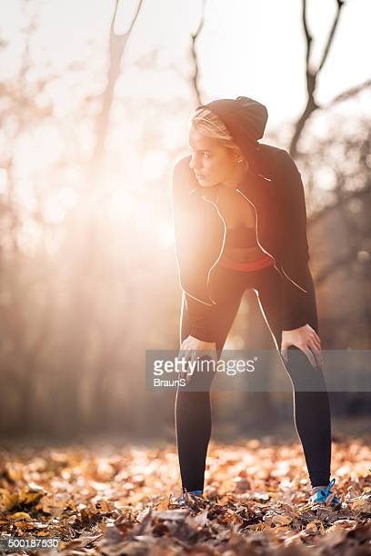 Athletic woman taking a breath after exercising at sunset.