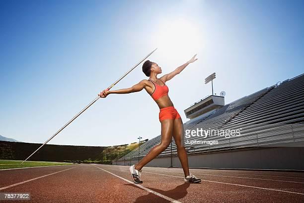 athletic woman throwing a javelin - やり投げ ストックフォトと画像