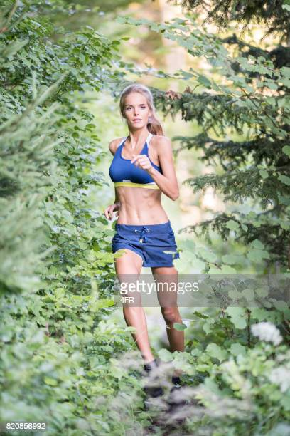 athletic woman trail running through a forest - running shorts stock pictures, royalty-free photos & images