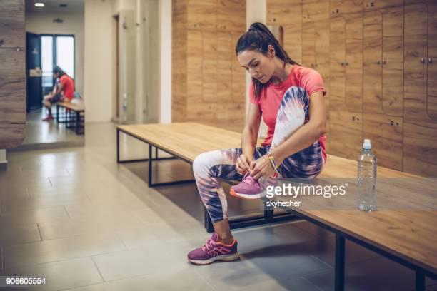 athletic woman tying shoelaces in dressing room before sports training. - shoelace stock pictures, royalty-free photos & images