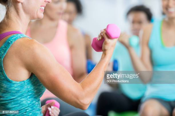 Athletic woman uses hand weight in gym