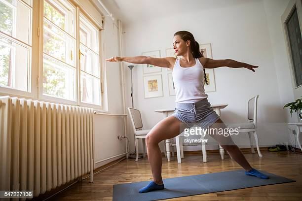 Athletic woman warming up while doing stretching exercises at home.