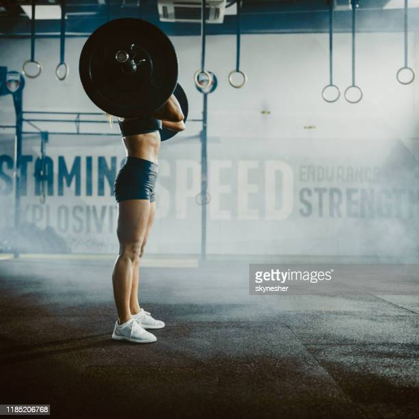 athletic woman with obscured face exercising strength with barbell in a health club. - obscured face stock pictures, royalty-free photos & images