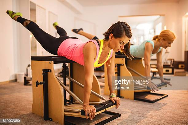 Athletic women exercising on Pilates stability chairs in health club.