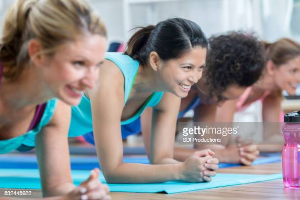 athletic women in a plank during exercise class - asian six pack stock photos and pictures