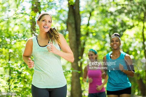 Athletic women running together on trail in sunny park