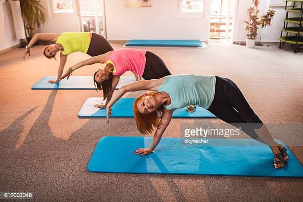athletic women stretching during pilates exercise class in health club. - petit groupe de personnes photos et images de collection
