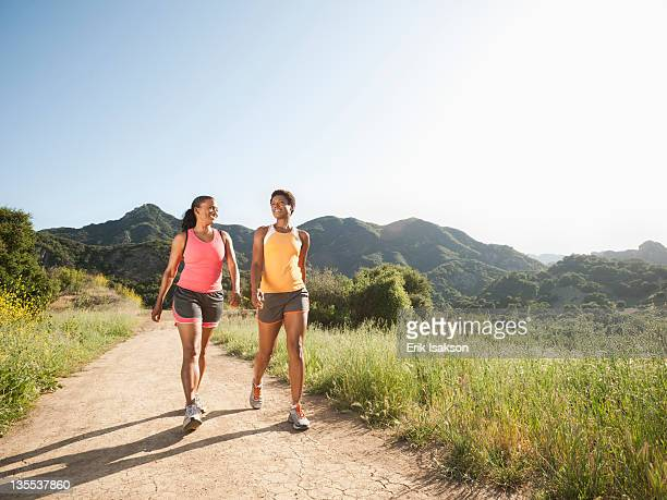 athletic women walking together on remote trail - americana azul fotografías e imágenes de stock
