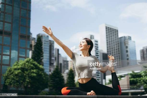athletic young asian woman practicing yoga outdoors in city park against urban cityscape in the morning - holy city park stock pictures, royalty-free photos & images