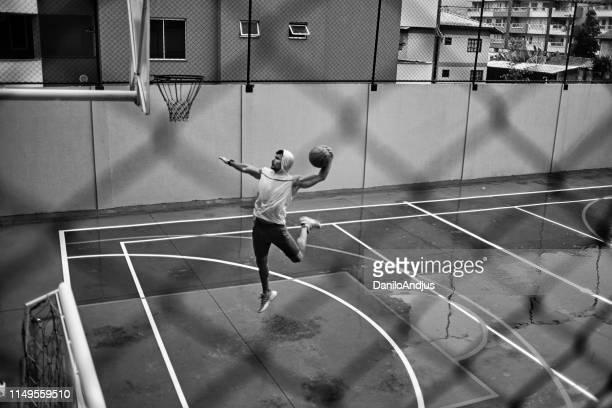 atletico giovane sbattere dunking su un tempo piovoso - tirare la palla foto e immagini stock