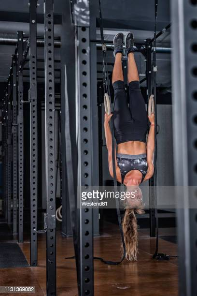 athletic young woman doing rings exercise at gym - extra long stock pictures, royalty-free photos & images