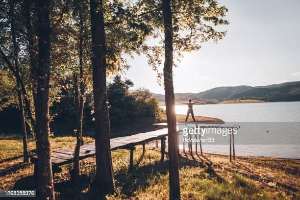 jeune femme d'athlétisme faisant le yoga près d'un lac de montagne au lever du soleil - spirituality photos et images de collection