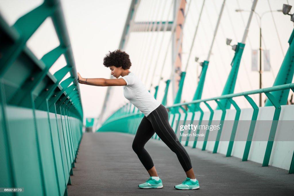 Athletic, young woman exercising on city bridge : Stock Photo