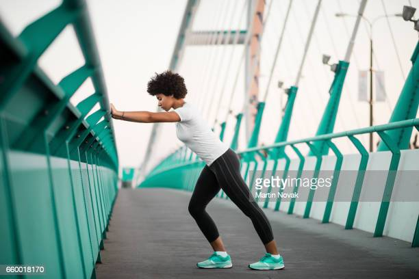 athletic, young woman exercising on city bridge - precalentamiento fotografías e imágenes de stock